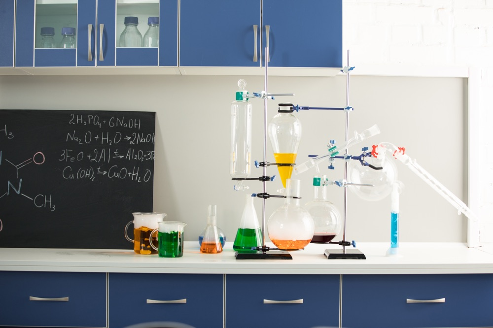 Science laboratory interior with colorful reagents and blackboard